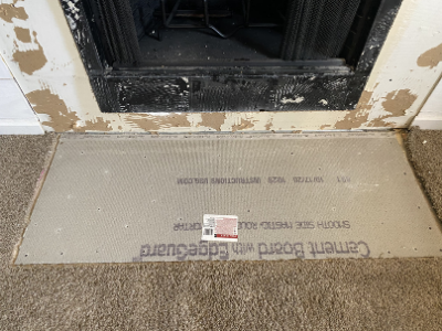 fireplace makeover cement board with edgeguard on floor in front of fireplace