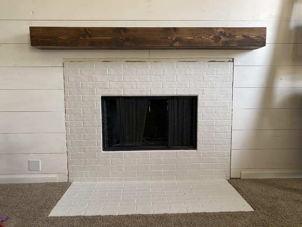 DIY Fireplace Makeover mantel mounted surrounded by faux brick tile