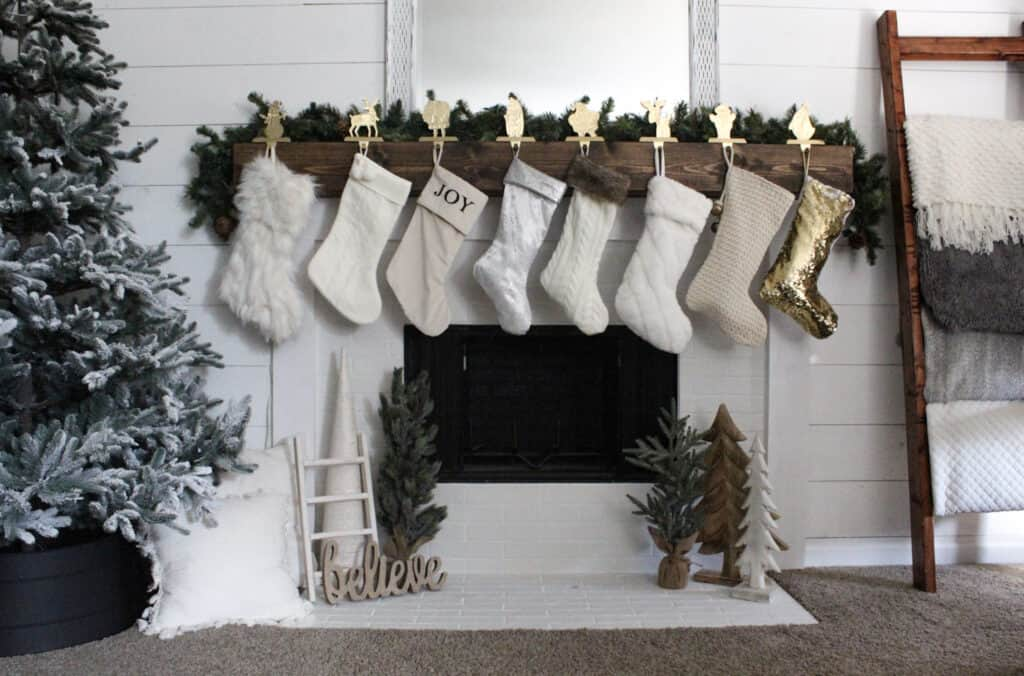 DIY Fireplace makeover after picture Kona stained wood mantle white brick tile white trim decorated with neutral colored christmas stockings