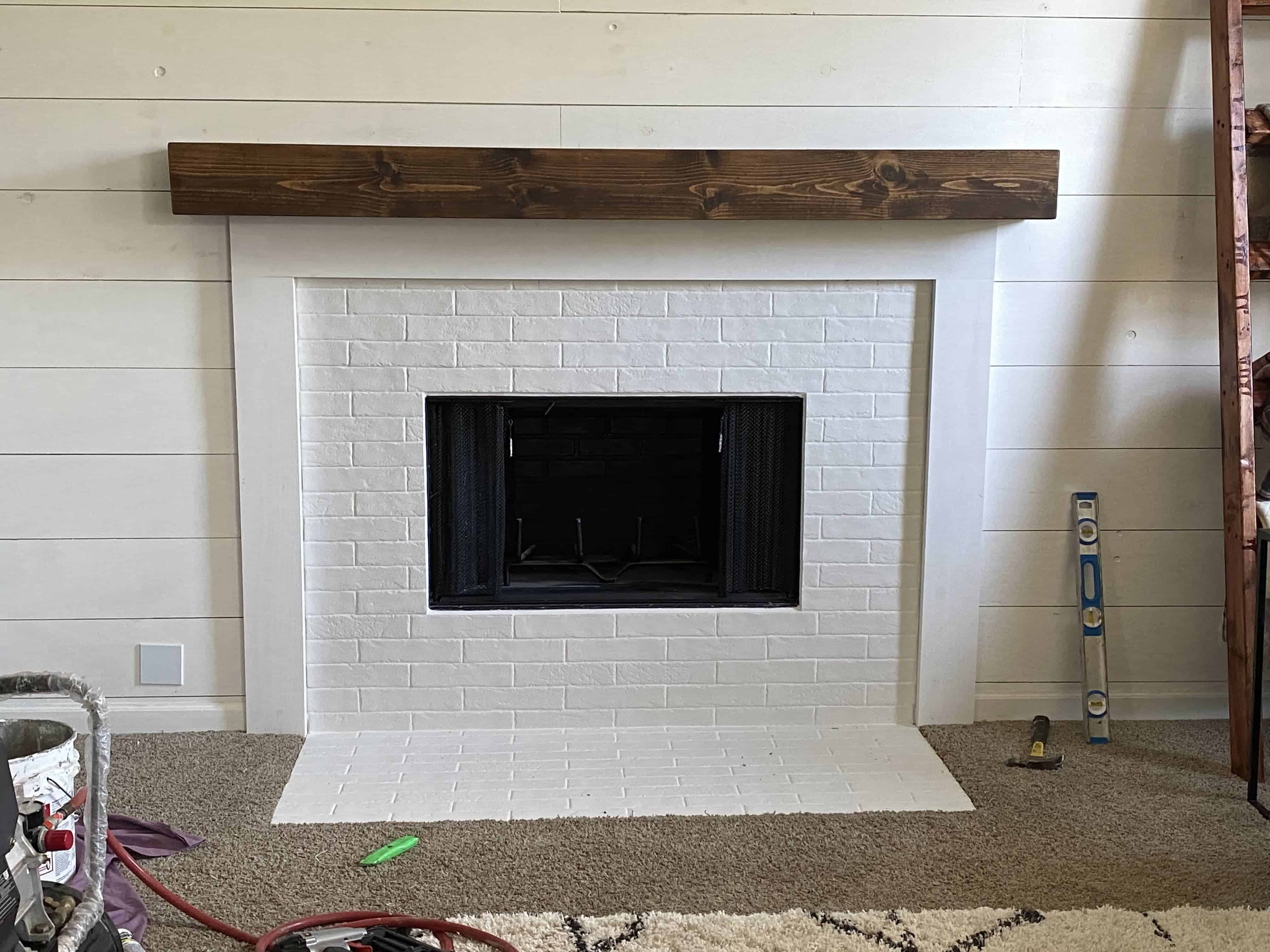 Faux brick fireplace with white tile and diy wood mantel