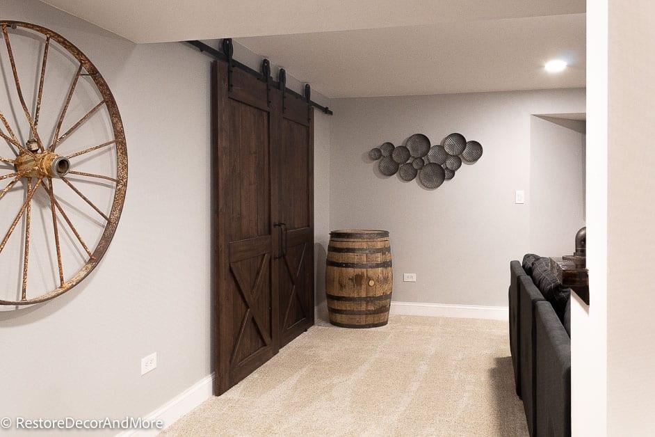 Whiskey barrel Wagon wheel and barn doors in finished basement