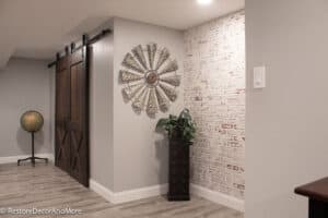 Globe on stand, double barn doors and faux brick wall in finished basement