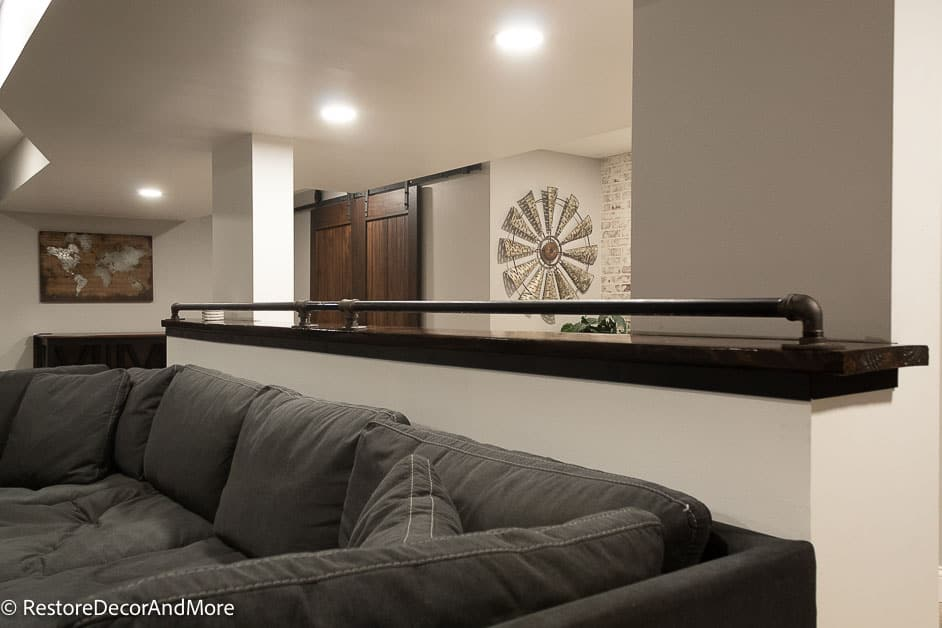 Finished basement behind couch bar with industrial pipe