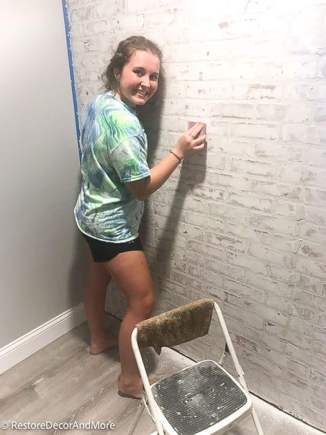 girl sanding faux brick wall