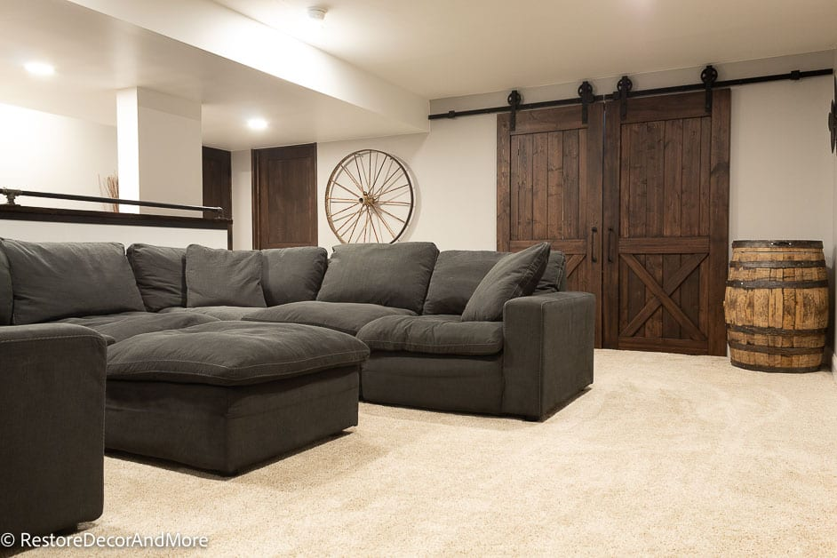 finished basement couch and view of barn door and whiskey barrel