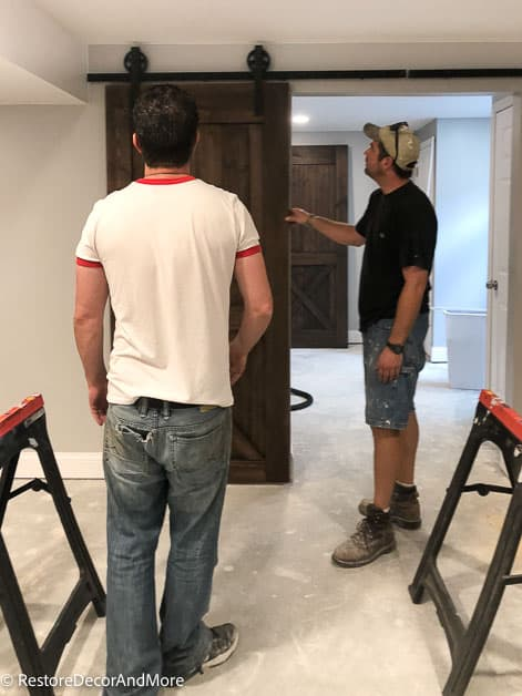 two guys installing barn doors