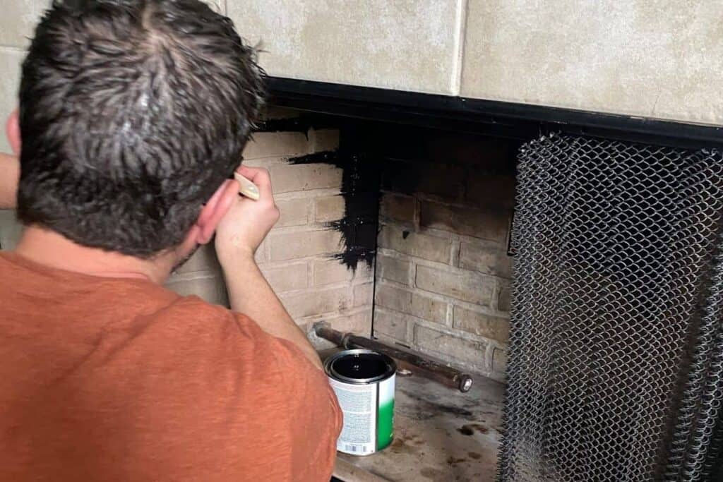 Man painting inside of fireplace with high heat paint brush on