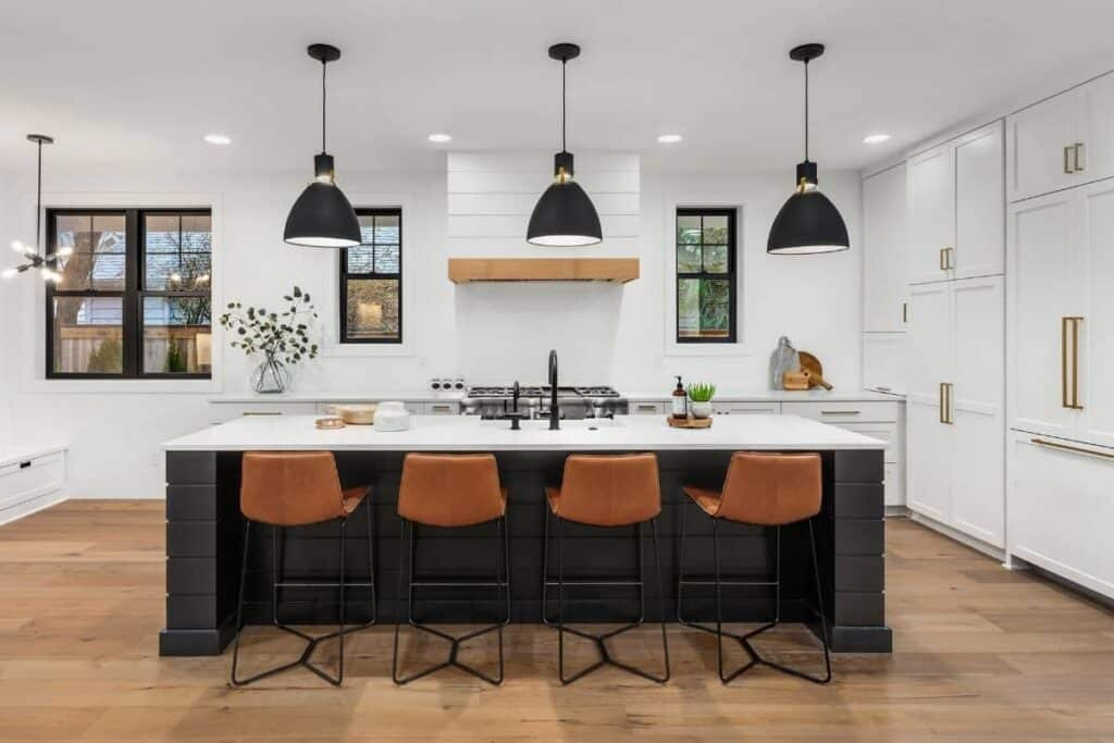 farmhouse style black lighting in kitchen with white cabinets, gold hardware, black island, brown leather bar stools