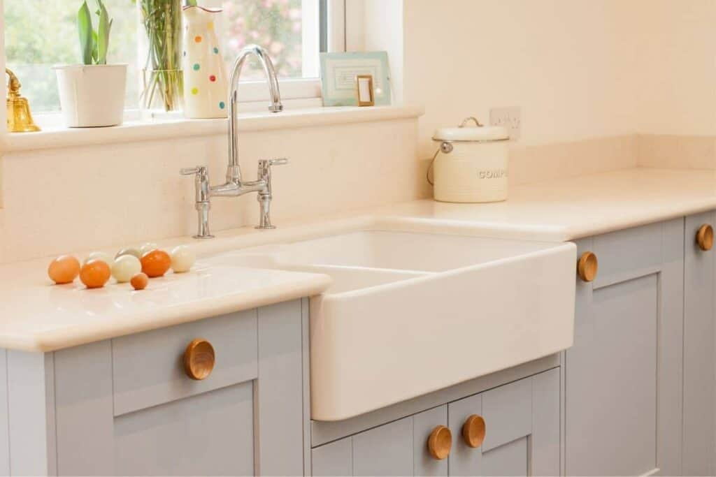 apron sink in kitchen with blue cabinets wood hardware