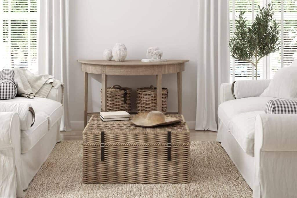 Farmhouse Style Living Room with neutral colors. White slipcover sofas and wood table, white curtains, plant in corner