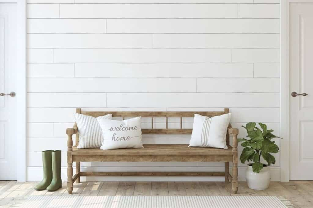 Farmhouse style white shiplap with wood bench and cream colored pillows