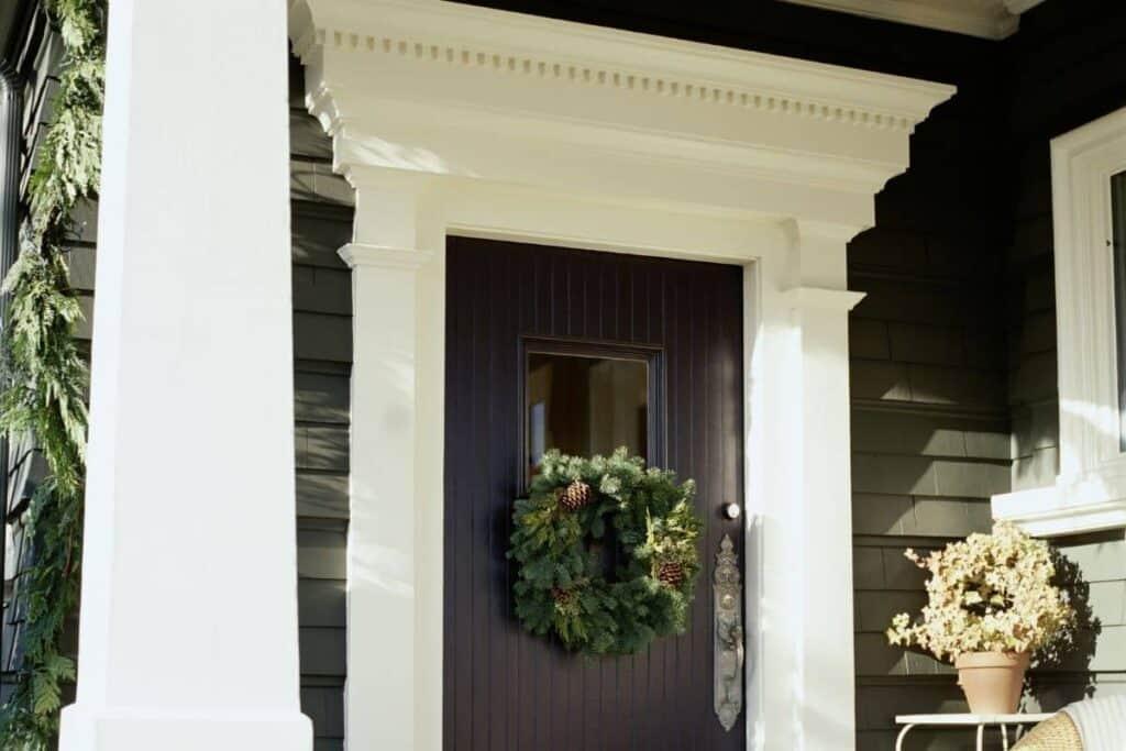 Black front door with green wreath DIY PROJECT on it