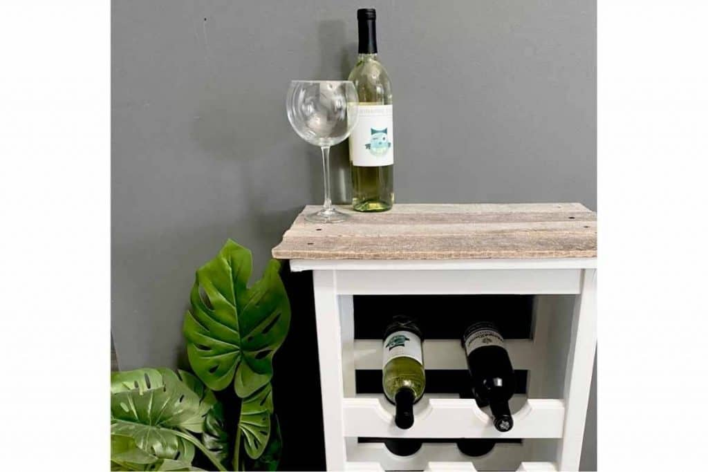 white wine rack with grey weathered pallet wood top wine glass and bottle of wine