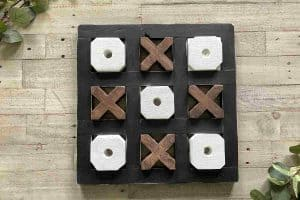 Table top wooden tic tac toe board with black frame white o's and brown x's