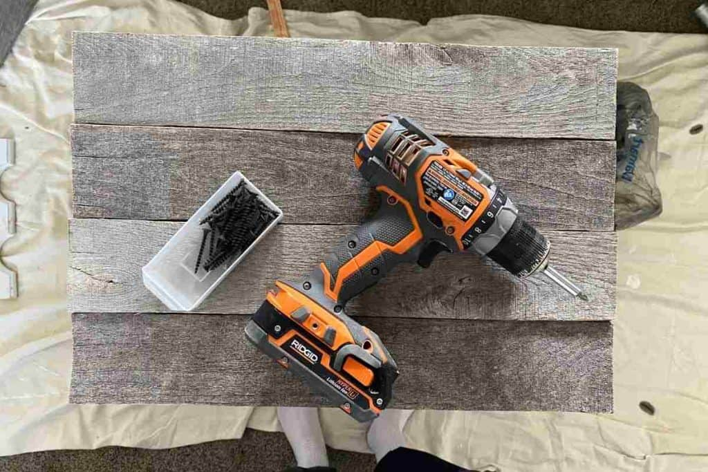 drill and screws laying on grey weathered pallet wood