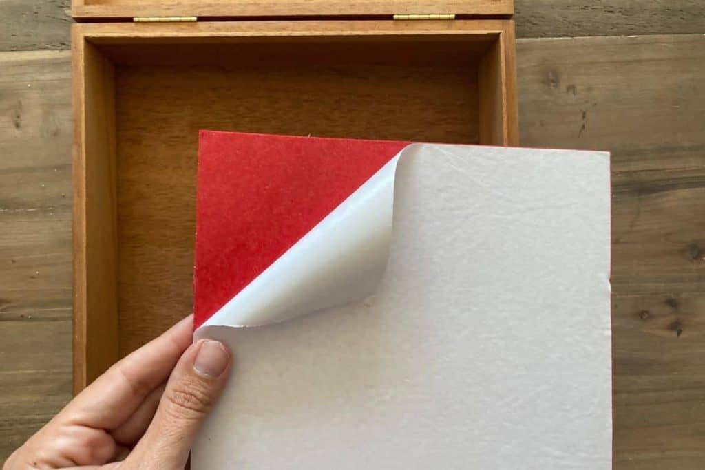 adhesive backing being removed from red felt