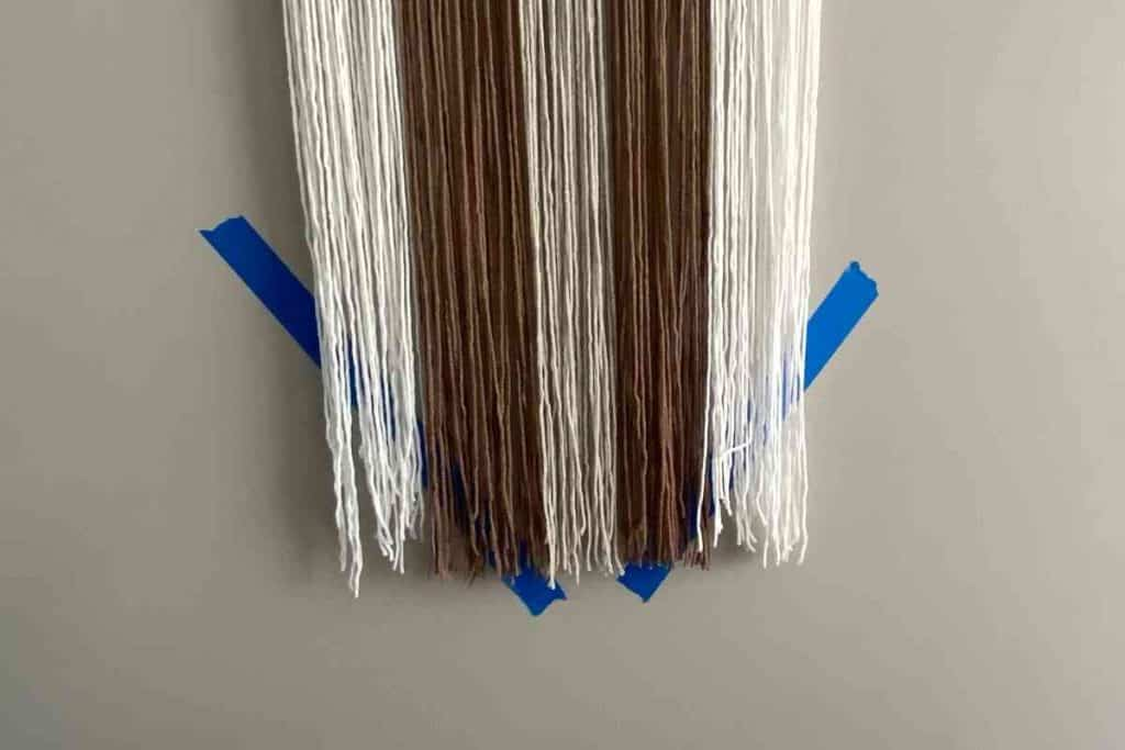 Trim Yarn wall hanging at an angle using painters tape as a guide