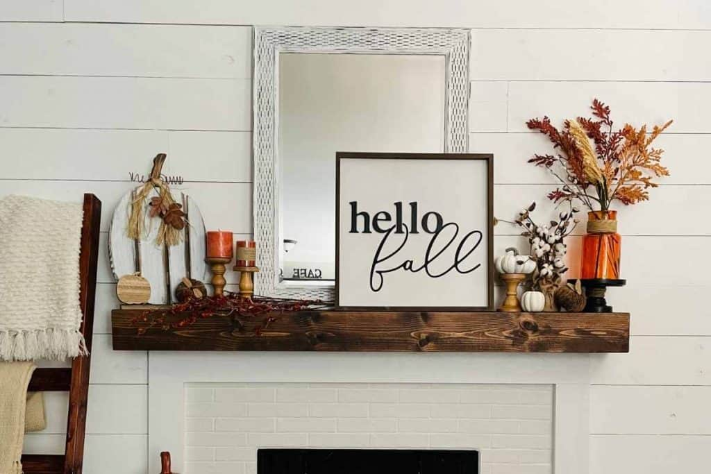fall farmhouse mantel with hello fall sign, white pumpkins, orange vase, and orange floral. also wood candle holders, orange candles