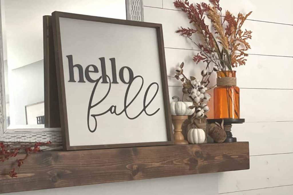 fall farmhouse mantel with hello fall sign, white pumpkins, orange vase, and orange floral