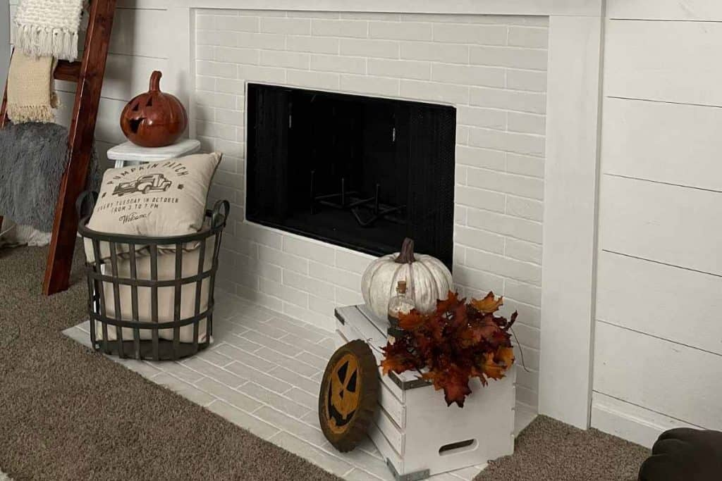 fireplace hearth decorated for fall with pumpkins, crate, basket, pillows and stool