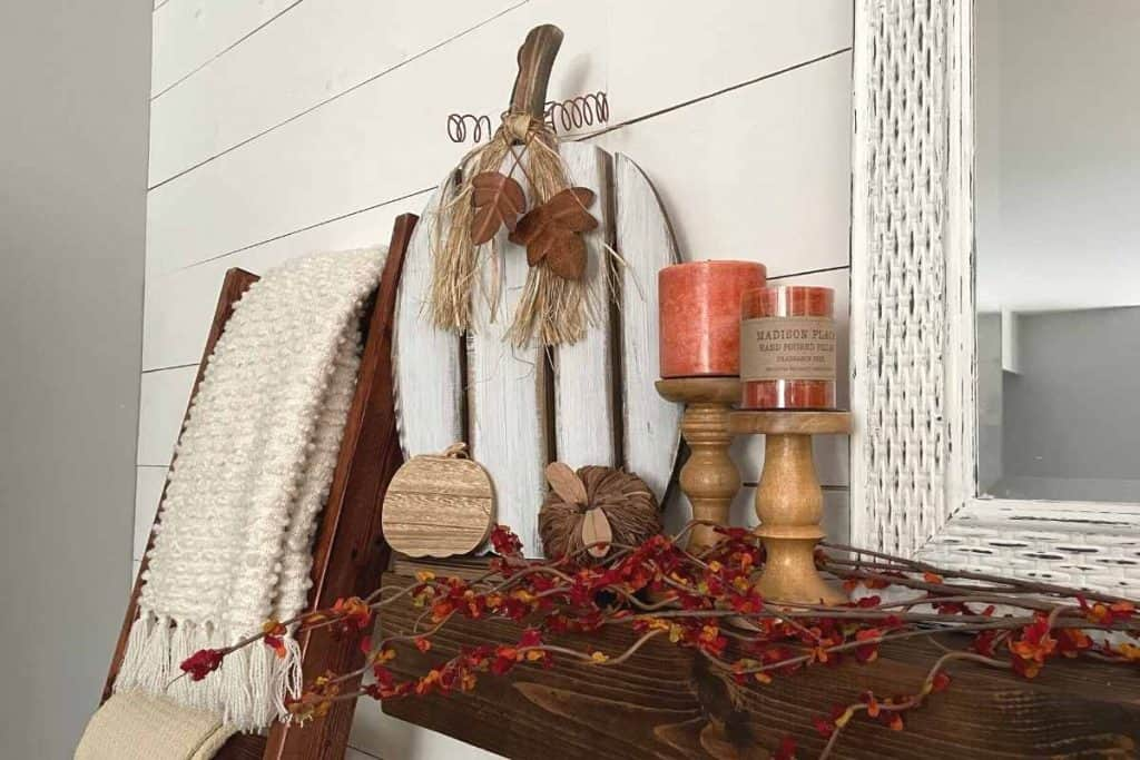 tall rustic wooden pumpkin on mantel along with candle holders, orange candles and wood pumpkins