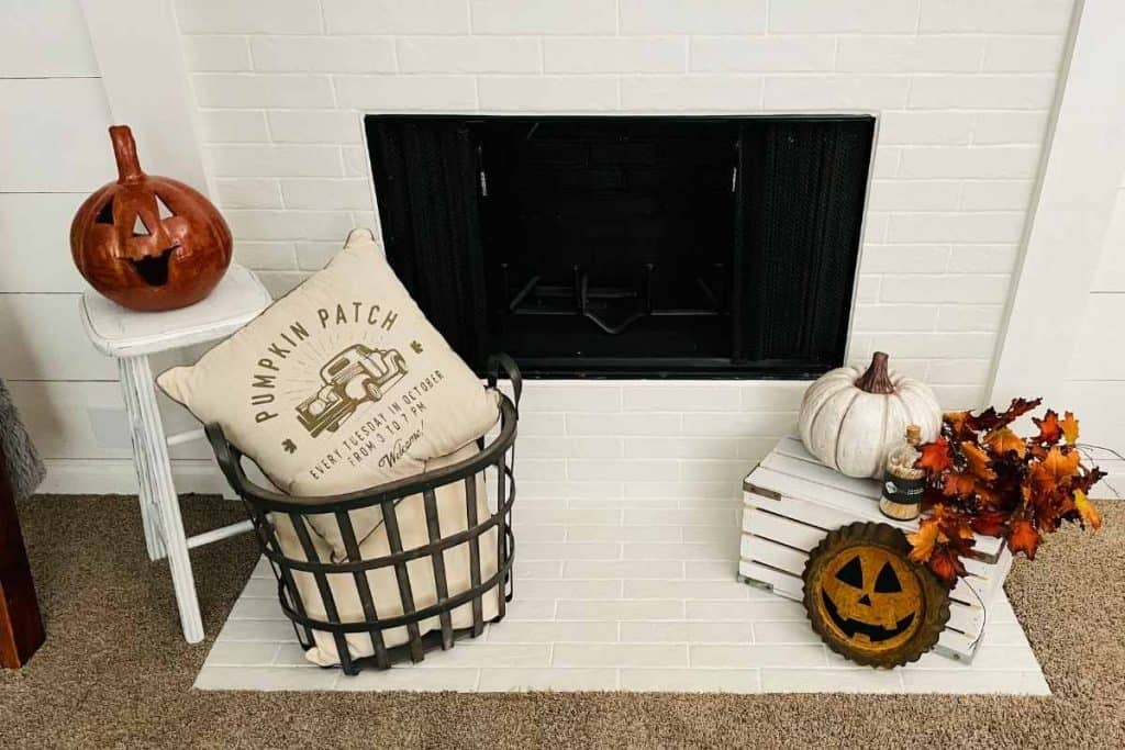 fall farmhouse mantel fireplace hearth with stool, basket, crate and pumpkins